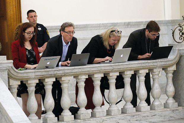 people work on laptops on balcony