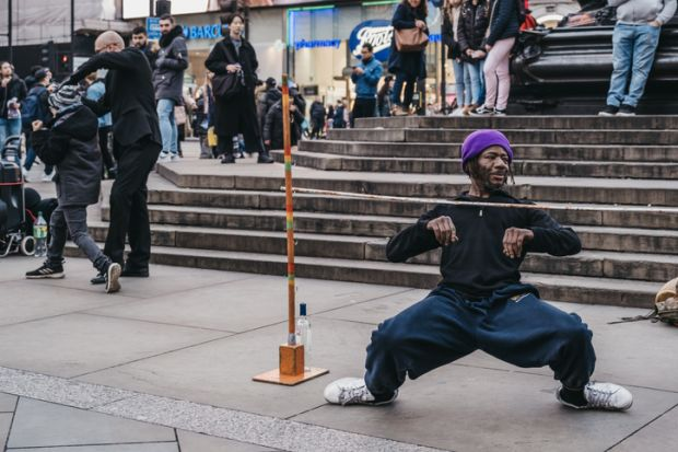 London, UK - November 24, 2019 Street performer limbo under the bar in Piccadilly Circus, one of the most popular tourist areas in London, UK, selective focus.