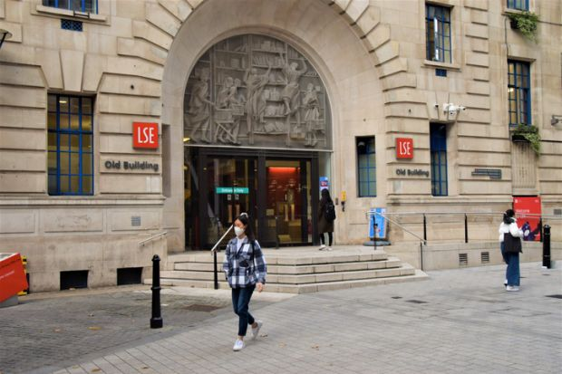 London, United Kingdom - November 13 2020 A student wearing a protective face mask walks past the LSE Old Building, London School of Economics and Political Science.
