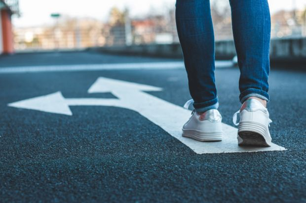 Make decision which way to go, walking on directional sign on asphalt road