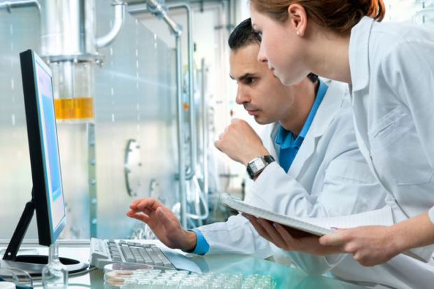 Male and female scientists at work in laboratory