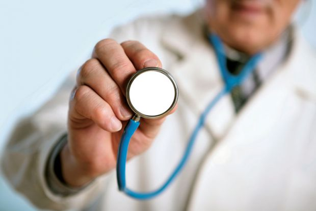 Male doctor holding stethoscope