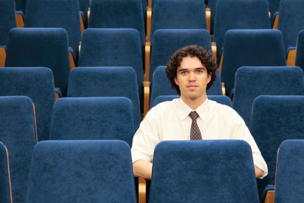 Male student sitting alone in lecture hall