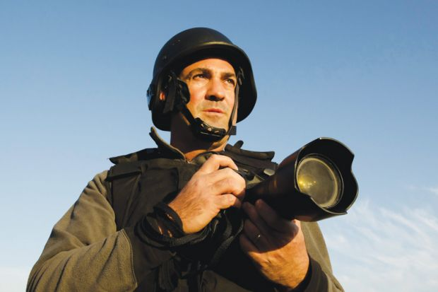 Male war photographer wearing protective helmet and vest