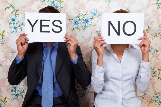 Man and woman holding yes/no cards in front of faces