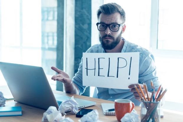 Man at desk holding 'Help' sign