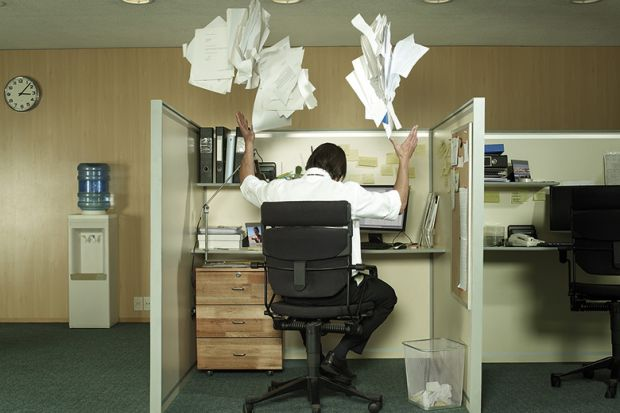 Man at desk throwing papers in the air