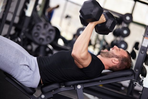 Man bench pressing with dumbbells