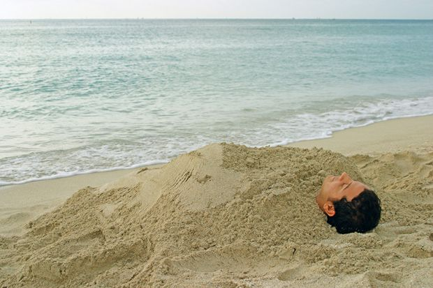 Man buried in sand on beach