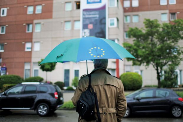 Man carrying a European Union (EU)-branded umbrella