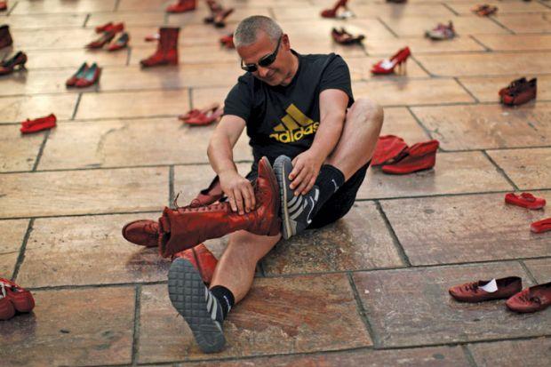 Man compares shoes, La Constitucion Square, Malaga, Spain