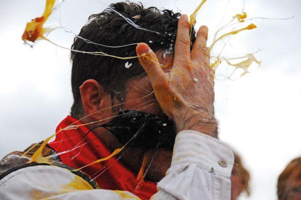Man cracking egg on forehead