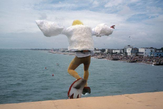 Man dressed as bird jumping into sea, Bognor Regis, England