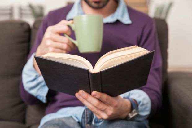 Man drinking coffee and reading book