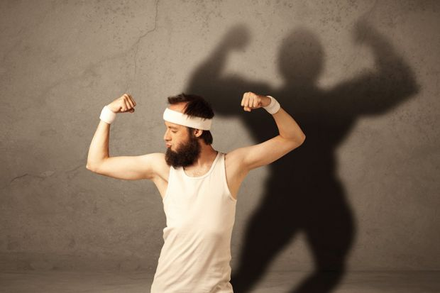 Man flexing muscles with shadow on wall