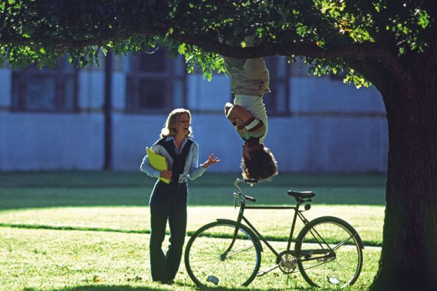 Man hanging upside-down from tree