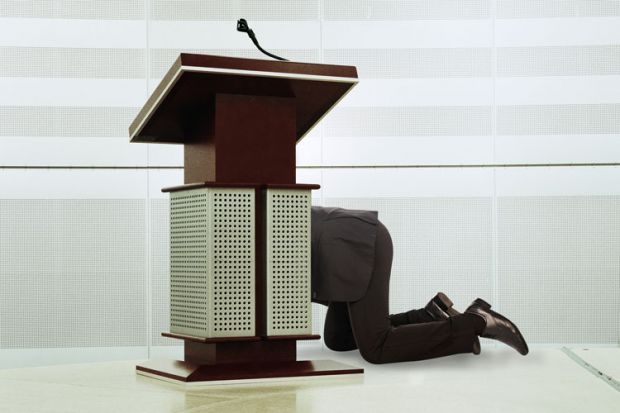 Man hiding behind podium