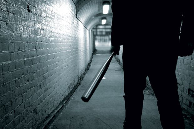 Man holding baseball bat in tunnel