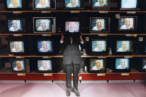 Man holding television in front of face in television shop