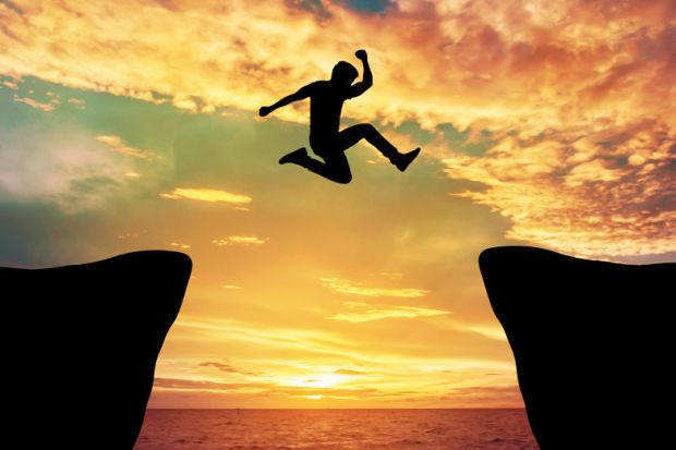 Man jumping between rocks against sunset