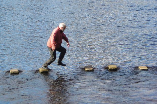 Man leaping across stepping stones in sea inlet