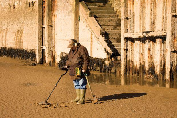 Man metal detecting on beach
