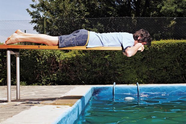 Man on diving board over swimming pool