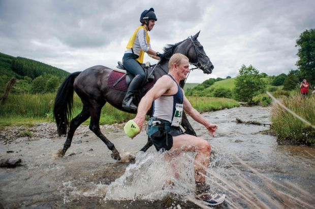 Man racing horse across shallow river