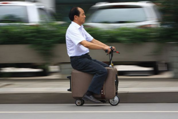 Man rides on electric suitcase