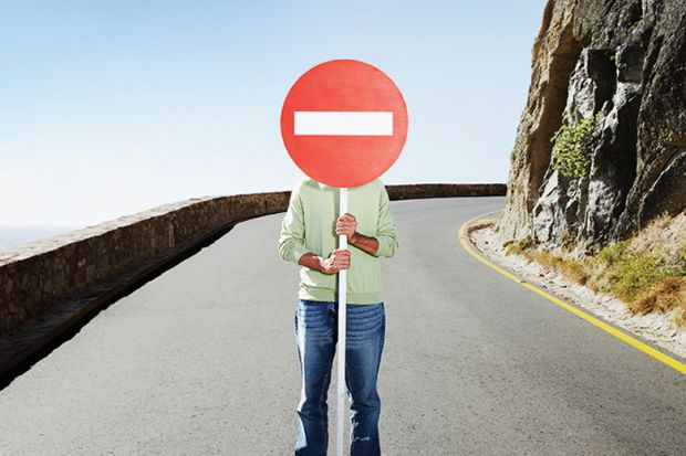 Man standing in road holding No Entry sign over face