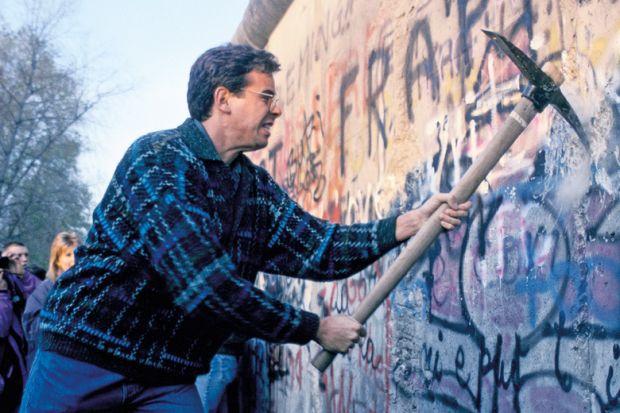 Man using pickaxe to break down Berlin Wall, 1989