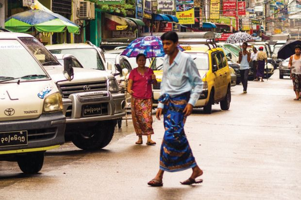 Man walking across congested street, Yangon, Myanmar