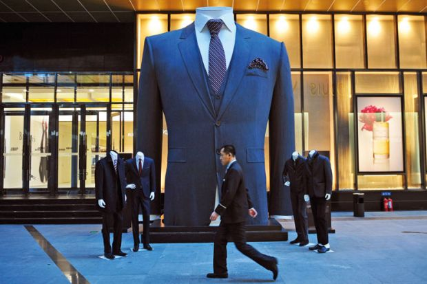 Man walks past huge suit, Shenyang, Liaoning province