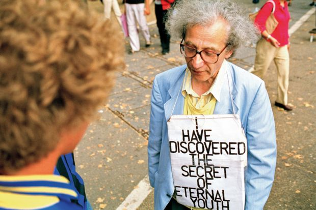 Man wearing 'I have discovered the secret of eternal youth' sign