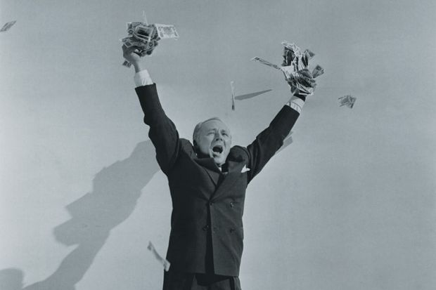 Man celebrating with hands full of cash