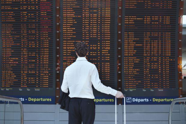 Man looking at airport departure board