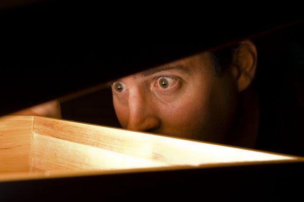 Man looking under box lid