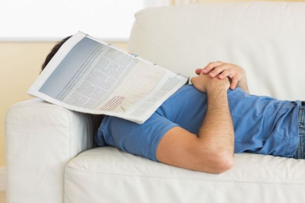 Man sleeping under newspaper