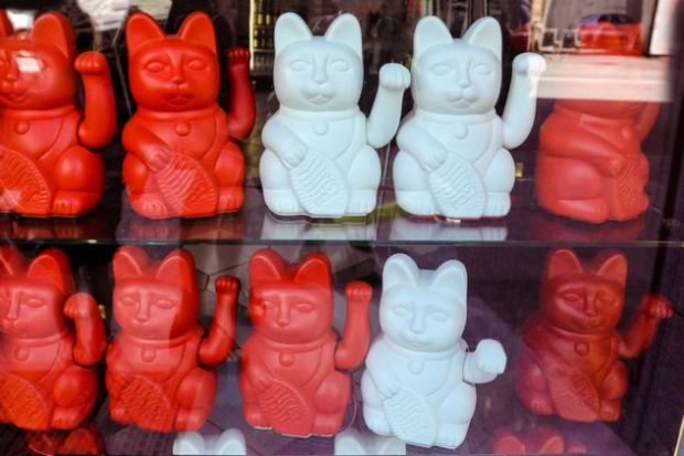 Maneki neko also known as chinese fortune cat. Showcase with welcoming souvenir cats beckoning to enter