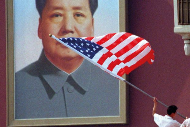 A worker installs an American flag in front of the portrait of China's late Chairman, Mao Zedong, which hangs on Tiananmen Gate in the centre of Beijing