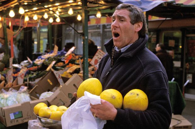 Market trader selling fruit, London
