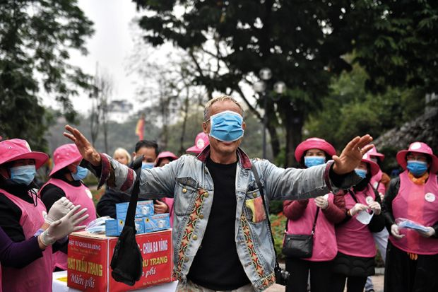Man with medical mask over eyes surrounded by a crowd of people
