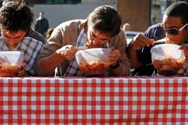 Men eating pasta in speed eating competition