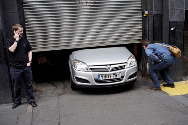 Men looking at car stuck under garage door