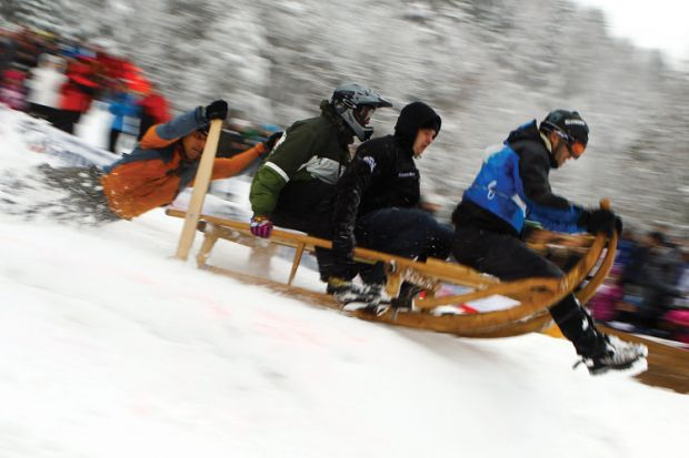 Men riding wooden sledge, Garmisch-Partenkirchen, 2012