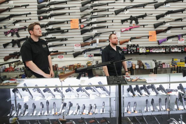 Men stand in front of display of firearms in gun store, Lake Barrington, Illinois