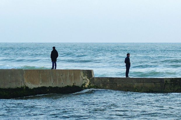 Men standing in opposite directions on seafront wall