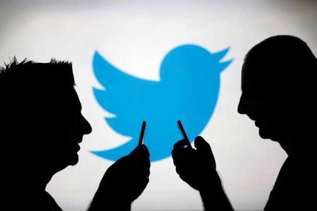 Men using smartphones against Twitter logo backdrop