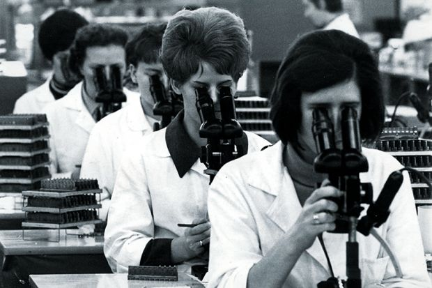Team of researchers with microscopes