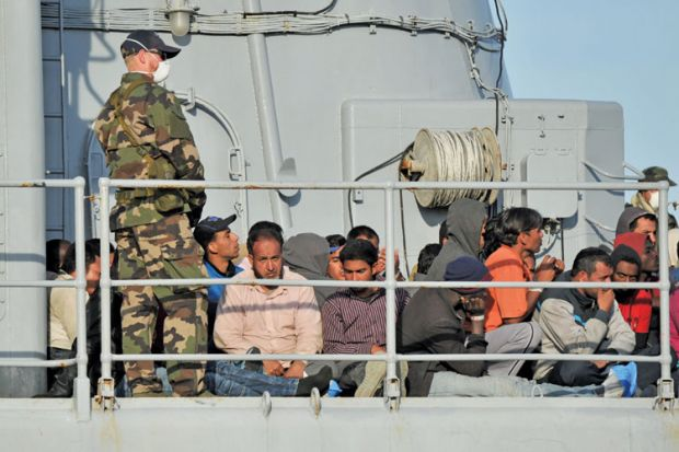 Migrants sitting on a rescue ship